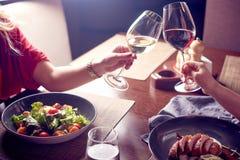 Jovens mulheres bonitas com vidros do vinho vermelho e branco no restaurante luxuoso Jantar ou almoço Comendo saladas e carne Imagem de Stock Royalty Free