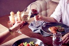 Jovens mulheres bonitas com vidros do vinho vermelho e branco no restaurante luxuoso Jantar ou almoço Comendo saladas e carne Imagens de Stock Royalty Free