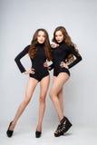 Jovens mulheres bonitas dos gêmeos em corpos pretos sobre o fundo branco Fotografia de Stock