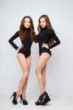 Jovens mulheres bonitas dos gêmeos em corpos pretos sobre o fundo branco Imagem de Stock