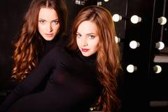 Jovens mulheres bonitas dos gêmeos em corpos pretos sobre o fundo escuro em um vestuario Fotografia de Stock Royalty Free