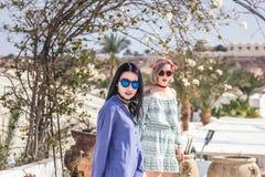 jovens mulheres bonitas nos óculos de sol que olham a câmera ao andar junto no recurso em Egito imagens de stock royalty free