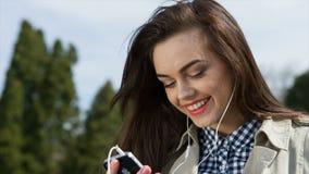 Jovens mulheres bonitas nos fones de ouvido que escutam vídeos de arquivo
