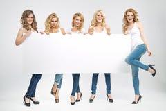 Jovens mulheres bonitas que guardam a placa fotos de stock royalty free