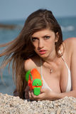 Jovens mulheres bonitas que jogam com a arma de água na praia Foto de Stock