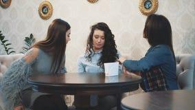 Jovens mulheres bonitas que sentam-se em um café Um tiro bonito e morno de uma menina caucasiano na roupa ocasional através de um video estoque