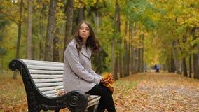 Jovens mulheres bonitas tristes que andam em torno e que sentam-se no banco no parque no outono, esperando alguém vídeos de arquivo