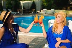 Jovens mulheres bonitos felizes com cocktail que riem e que têm o divertimento perto da piscina fotos de stock royalty free