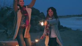 Jovens mulheres com os chuveirinhos contra a costa da noite vídeos de arquivo