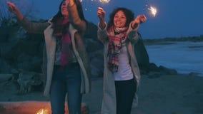 Jovens mulheres com os chuveirinhos contra a costa da noite filme
