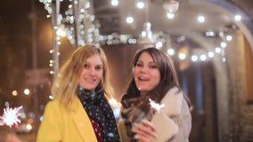 Jovens mulheres com os chuveirinhos no fundo da cidade da noite video estoque