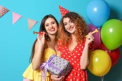 Jovens mulheres com ventiladores do partido e caixa de presente no fundo da cor Celebração do aniversário Fotografia de Stock Royalty Free