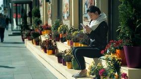 Jovens mulheres da forma da beleza que texting com o telefone esperto que senta-se em um banco na rua video estoque