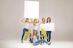 Jovens mulheres de fascínio que guardam placas Fotografia de Stock