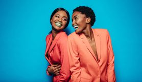 Jovens mulheres de riso na roupa à moda Foto de Stock