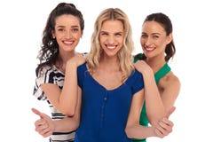 3 jovens mulheres de riso que mostram a aprovação manuseiam acima do sinal Fotos de Stock Royalty Free