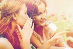 Jovens mulheres de sorriso que bisbilhotam no café exterior imagens de stock royalty free