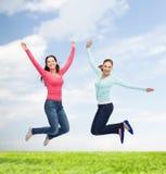 Jovens mulheres de sorriso que saltam no ar Fotografia de Stock Royalty Free
