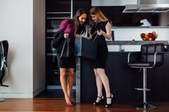 Jovens mulheres de sorriso que vestem a roupa elegante formal que olha no saco de compras que está no apartamento moderno imagem de stock royalty free