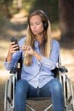 Jovens mulheres deficientes bonitas que escutam a música no parque foto de stock royalty free