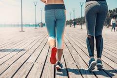 Jovens mulheres do ajuste dois que movimentam-se perto do mar fotos de stock