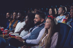 Jovens mulheres e homens que passam o tempo livre no cinema junto Imagens de Stock