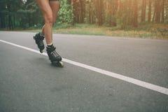 Jovens mulheres e patins de rolo magros e 'sexy' Férias ativas do verão na cidade Esportes extremos Imagens de Stock