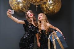 Jovens mulheres elegantes de encantamento nos vestidos pretos luxuosos que fazem o selfie com os bal?es grandes com ourop?is dour imagens de stock royalty free