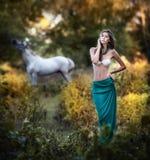 Jovens mulheres em uma saia longa azul e em um sutiã branco no por do sol na floresta com um cavalo branco imagem de stock