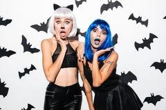 Jovens mulheres emocionais em trajes do Dia das Bruxas Imagens de Stock Royalty Free