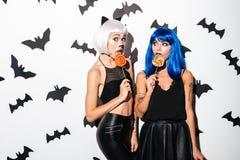 Jovens mulheres emocionais em trajes do Dia das Bruxas Fotos de Stock