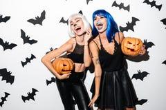 Jovens mulheres emocionais em trajes do Dia das Bruxas Foto de Stock