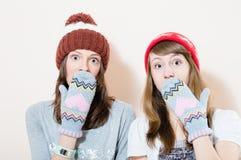 2 jovens mulheres encantadores no inverno tampam a vista confundida luvas in camera no retrato branco do fundo Foto de Stock