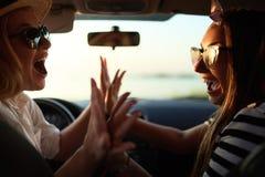 Jovens mulheres entusiasmados felizes que conduzem no carro e que fazem o gesto altamente cinco na viagem das férias de verão Dua foto de stock royalty free