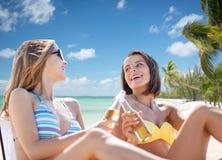 Jovens mulheres felizes com bebidas que tomam sol na praia Imagens de Stock Royalty Free