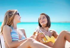 Jovens mulheres felizes com bebidas que tomam sol na praia Imagens de Stock