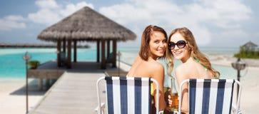 Jovens mulheres felizes com bebidas que tomam sol na praia Fotos de Stock