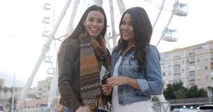 Jovens mulheres felizes do divertimento na frente de uma roda de ferris Fotografia de Stock