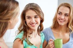 Jovens mulheres felizes que bebem o chá com doces em casa Fotos de Stock Royalty Free