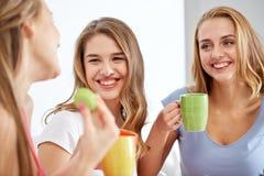 Jovens mulheres felizes que bebem o chá com doces em casa Fotos de Stock