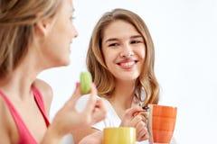 Jovens mulheres felizes que bebem o chá com doces em casa Fotografia de Stock