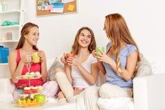 Jovens mulheres felizes que bebem o chá com doces em casa Imagem de Stock