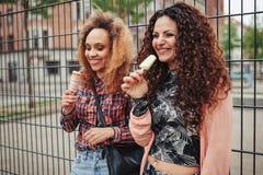 Jovens mulheres felizes que comem o gelado - fora Imagem de Stock Royalty Free