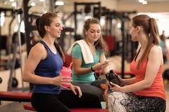 Jovens mulheres felizes que descansam após o treinamento da aptidão no gym Fotografia de Stock