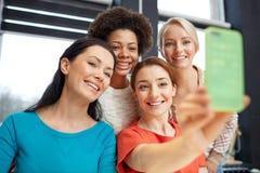 Jovens mulheres felizes que tomam o selfie com smartphone fotografia de stock royalty free