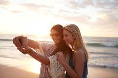 Jovens mulheres felizes que tomam o selfie na praia imagens de stock royalty free