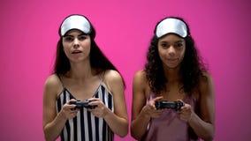 Jovens mulheres no desgaste do sono que guarda manches e que joga o jogo de v?deo, emo??es fotografia de stock