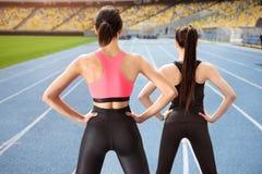 Jovens mulheres no sportswear que exercitam no estádio da pista de atletismo Imagem de Stock Royalty Free