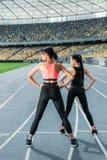 Jovens mulheres no sportswear que exercitam no estádio da pista de atletismo Fotografia de Stock Royalty Free