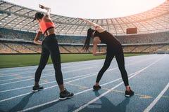 Jovens mulheres no sportswear que exercitam no estádio da pista de atletismo Fotos de Stock Royalty Free